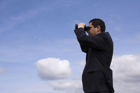 Businessman looking through binoculars with a blue sky as background Stock Photo - 2912661
