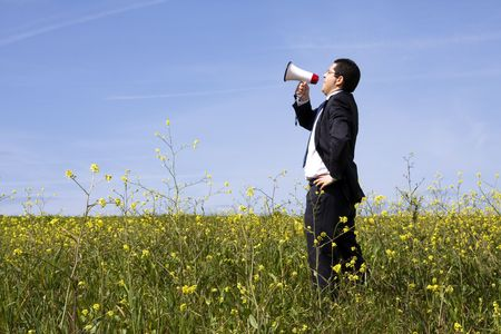Businessman speaking with a megaphone in a field photo