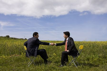 two businessman making a deal with a handshake at the field photo