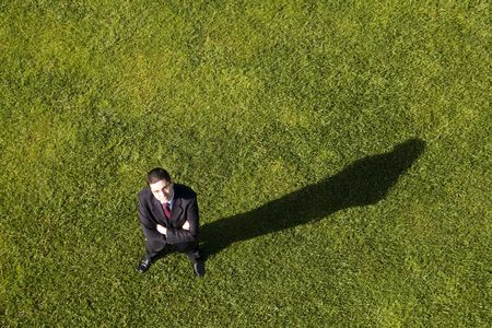 important people: Above view of a businessman standing on the grass (with copy space)