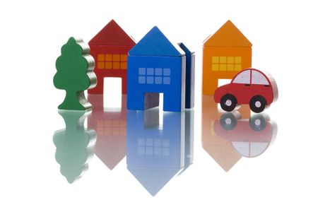 automobile insurance: colorful toy houses, car and tree isolated on white with reflection (selective and soft focus) Stock Photo