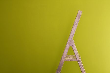 a construction ladder on a green wall Stock Photo - 3023849