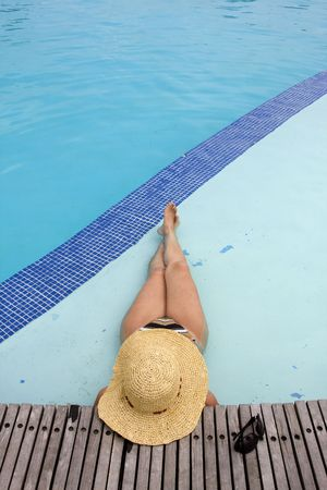 woman with a hat relaxing at the pool photo