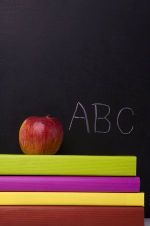 apple over a stack of books next to a chalkboard photo