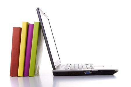 a laptop next to a stack of colorful books Stock Photo - 3473323