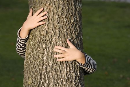 young generation embracing nature, with a hug at a tree Stock Photo