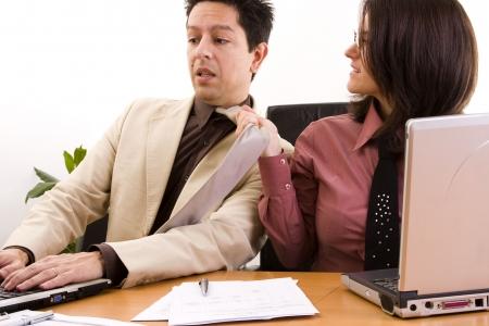 acoso laboral: acoso en el lugar de negocios de su pareja empujando su corbata