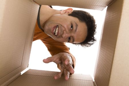 out of the box: young men reaching something inside a cardboard box