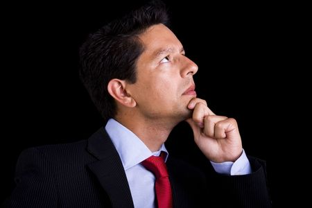 businessman thinking, looking to the copyspace (isolated on black) photo