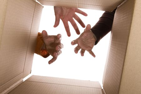 cardbox: inside view of cardboard box with three hands trying to reach the content (selective focus)