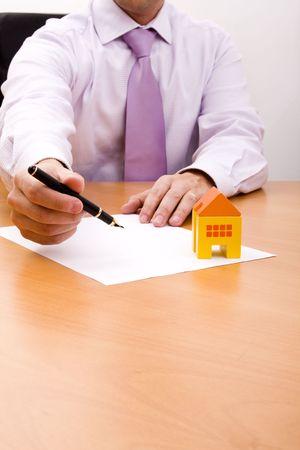 investment real state: hombre de negocios la venta de una nueva casa en su oficina (atención selectiva)