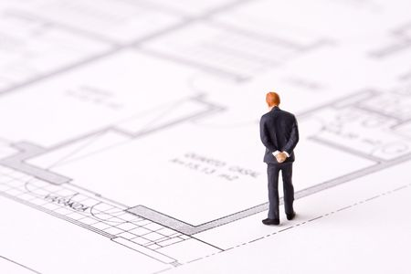 miniature people: small businessman examining an architech blueprint (selective focus) Stock Photo