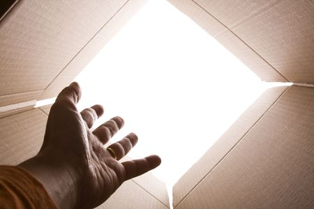 out of the box: inside view of cardboard box with a hand trying escape (selective focus) Stock Photo