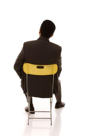 asiento: hombre de negocios de nuevo sentado en una silla amarilla mirando hacia el espacio de copia