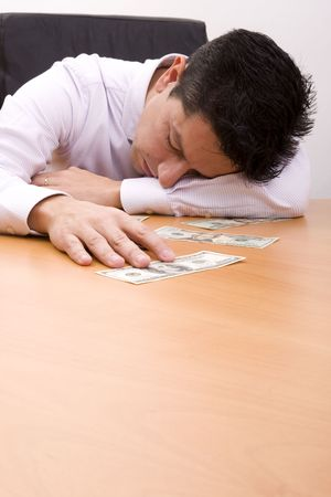 Businessman sleeping at the office with his hand on the money Stock Photo - 4572286