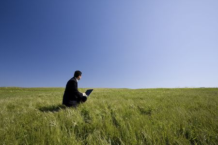 Businessman working with a laptop outdoor on a field photo