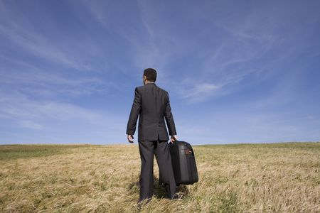 distant work: businessman with his luggage outdoor in the field