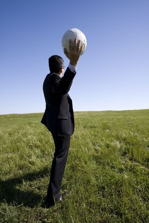 businessman in the field trowing a soccer ball photo
