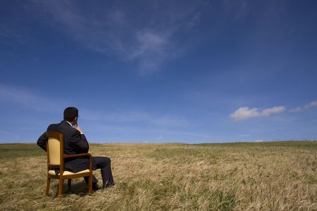 businessman sitting in a chair in outdoor looking to the field photo