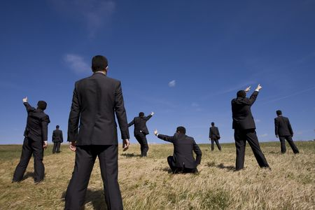 a group of businessman at the field searching for something photo