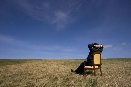 blue sky thinking: businessman sitting in a chair in outdoor looking to the field