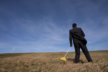 distant work: businessman cleaning the field with a broom Stock Photo
