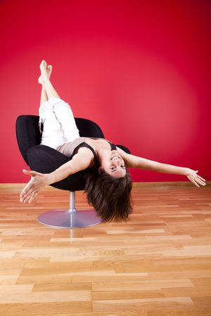 young woman enjoying her new house, upsidedown on her couch Stock Photo - 4892334