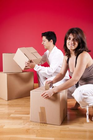 young leave: young couple packing some boxes inside there house