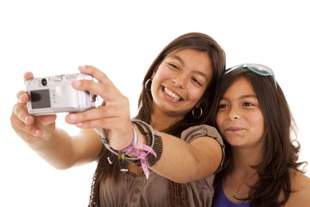 taking photo: two young sisters making a photo of them self (selective focus) Stock Photo