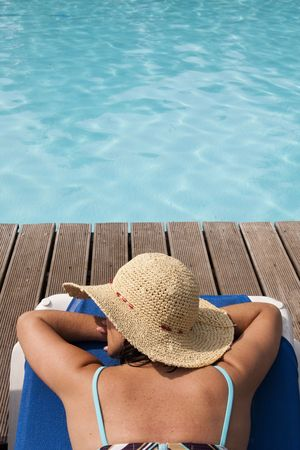 woman with a hat relaxing at the pool