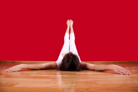 woman laying on the floor of her house with her legs up next to a red wall photo