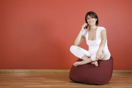 woman talking on the telephone next to a red wall Stock Photo - 4951570