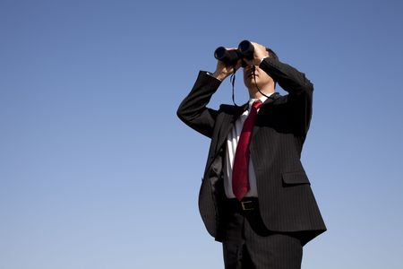 looking ahead: Businessman looking through binoculars with a blue sky as background