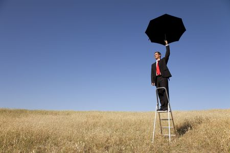 step ladder: businessman over a step ladder with an open umbrella over his head Stock Photo