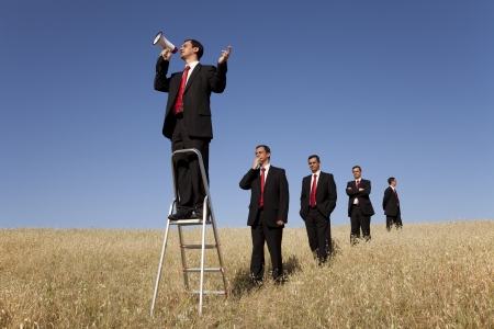 a group of businessman in the field getting in line for there time to speak  photo