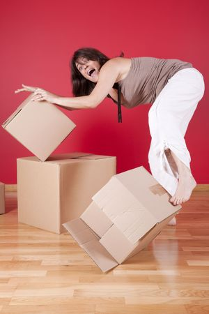 young woman trying to hold some cardboard boxes from falling photo