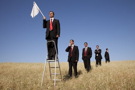 loss leader: a group of businessman in the field getting in line for there time to surrendering Stock Photo