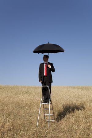 businessman over a step ladder with an open umbrella over his head photo