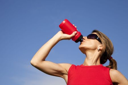 hot water bottle: young woman drinking water after doing some exercise