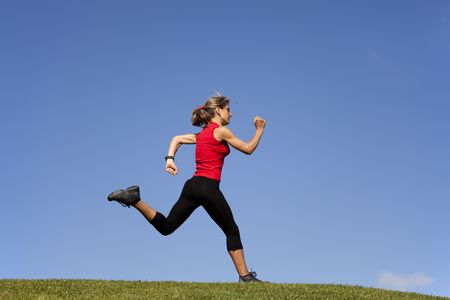 young woman running at the top of a hill photo