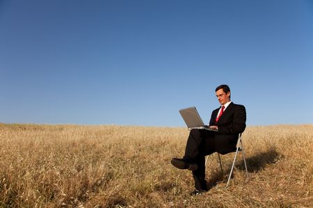 businessman working with his laptop outside in the field photo