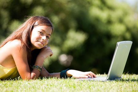 little girl studing with her laptop at the park photo