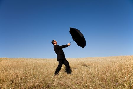 businessman holding a umbrella at the field photo