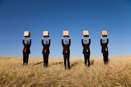 thinking outside the box: five businessman lineup holding a cardboard box over his head