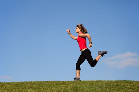 achivement: young woman running at the top of a hill