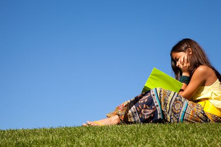 young female child at the park reading a book photo