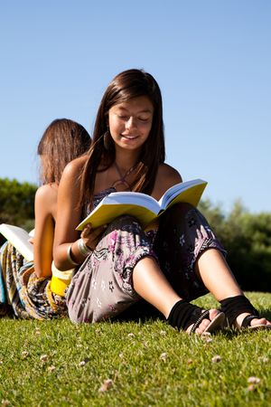 two young sisters at the park reading a book Stock Photo - 5474438
