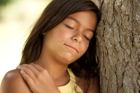 young female child enjoying nature with her head next to a tree photo