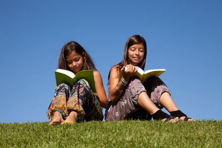 two young sisters at the park reading a book Stock Photo - 5595480