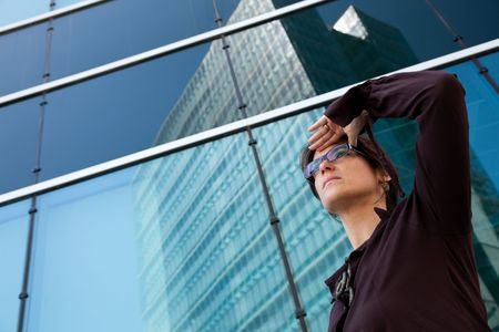businesswoman looking away next to her office building photo